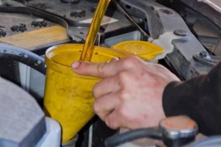 adding oil into running car